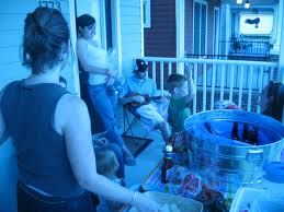 two women on the porch of a house with several children and a kiddie pool