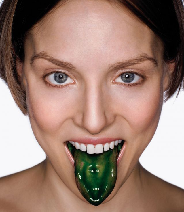 Young woman with slimy green tongue