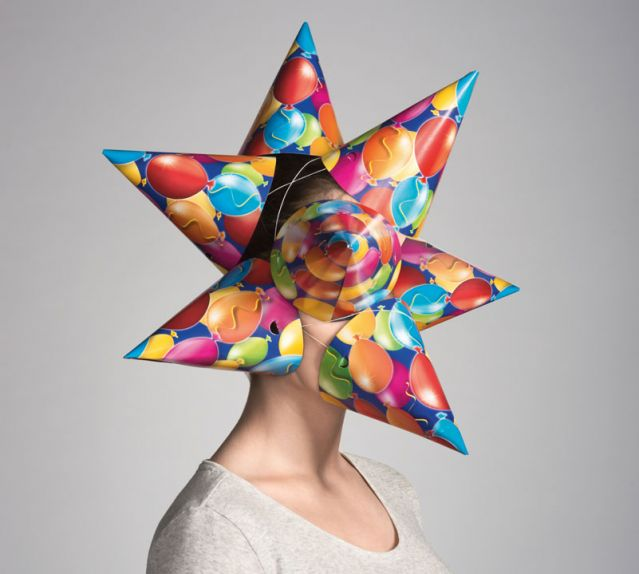 Image: Woman with cone party hats covering her face and head